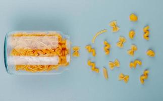 top view of macaronis as farfalle fusilli tagliatelle penne pipe-rigate spilling out of jar on blue background