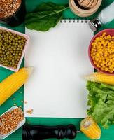 top view of note pad with corns corn seeds green peas spinach lettuce and salt around on green background with copy space