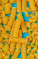 top view of macaronis as pipe-rigate ziti and fusilli on blue background