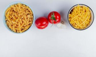 top view of macaronis as rotini and tagliatelle with tomatoes and garlic on white background with copy space