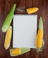 top view of note pad with whole and cut corns on wooden background