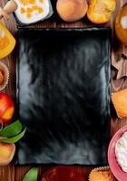 Vista superior de la placa oblonga con queso cottage melocotón cupcake alrededor sobre fondo de madera foto