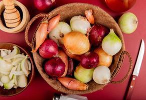 Vista superior de las cebollas en la canasta con pimienta negra, cebolla en rodajas en un tazón, sal, mantequilla y un cuchillo alrededor sobre fondo rojo.