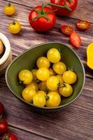 side view of yellow tomatoes in bowl with red ones on wooden background photo