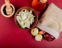 top view of onions spilling out of sack with sliced ones in bowl and melted butter with black pepper seeds in garlic crusher on red background photo