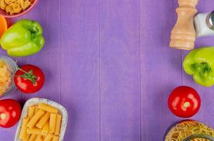 top view of macaronis as spaghetti penne and others with tomato pepper salt on sides on purple background with copy space