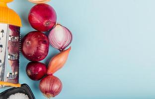 top view of onions with salt and grater on left side and blue background with copy space