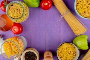 top view of macaronis as spaghetti vermicelli tagliatelle and others with tomato black pepper pepper butter set in round shape on purple background with copy space