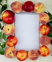 Top view of peaches around a notepad on white background decorated with leaves with copy space photo