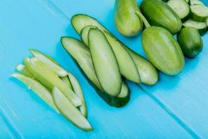 side view of whole cut sliced cucumbers on blue background