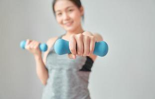 Woman wearing sportswear and dumbbell