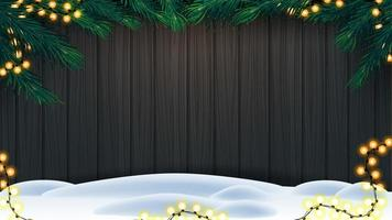 Christmas background, wooden fence of boards with frame of Christmas tree branches, garland of yellow bulb lights and snow on floor
