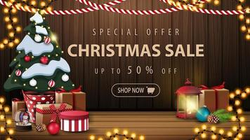 Special offer, Christmas sale, up to 50 off, beautiful discount banner with Christmas decor, garlands, vintage lantern and Christmas tree in a pot with gifts near the wooden wall vector