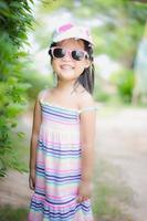 Retrato de linda niña asiática lleva gafas de sol y un sombrero en el parque