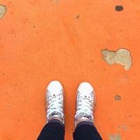 Persona que lleva zapatillas de pie sobre el piso naranja foto