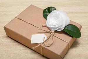 caja de regalo con etiqueta en blanco y flor blanca