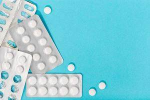 Pastillas de medicina sobre fondo azul.