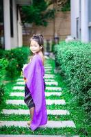 Happy asian little girl in Thai period dress standing in the park