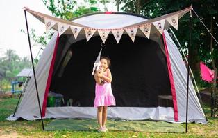 Little Asian girl standing in front of tent while going camping
