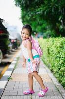 Portrait of happy little girl with backpack standing on footpath in the park