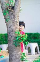Little girl sneaking behind the tree in the park