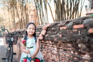 Cute little Asian girl in dress holding a red rose in the park photo