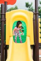 niña divirtiéndose para jugar al control deslizante en el patio de recreo en verano