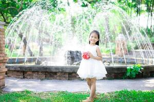 Cute little Asian girl in white dress holding a red gift in the park