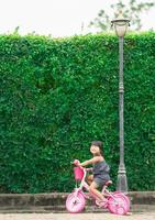 niña feliz andar en bicicleta en el parque