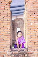 Little Asian girl in Thai period dress standing in ancient remains