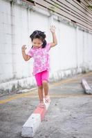 Little asian girl walking on the curb and trying to keep her balance