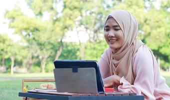 Beautiful Muslim girl sitting happily in the park. Muslim woman smiling in garden lawn. Lifestyle concept of a  confident modern woman