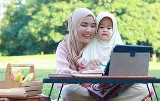 Muslim mothers and daughters enjoy their holidays in the park. Love and bond between mother and child