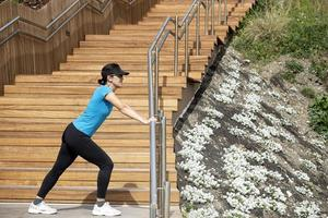 woman running in a blue t-shirt doing stretching exercises next to a wooden staircase. healthy living concept.