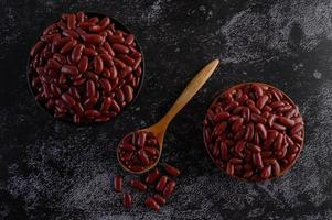 Red beans in wooden bowls on black kitchen surface