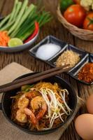 Pad thai shrimp in a black pan with eggs and seasoning