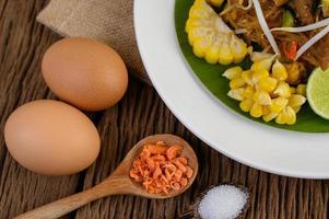 Pad thai con limón, huevos y condimentos sobre una mesa de madera