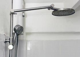 Ducha de baño en la pared de azulejos blancos