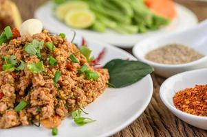 Minced pork salad with spices on a wooden table