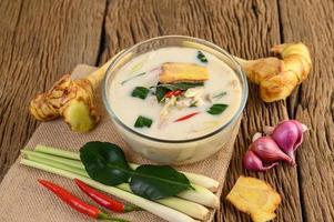 tom kha kai, sopa de coco tailandesa sobre tabla de cocina de madera