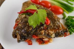 Deep-fried fish head topped with chilis on a white plate