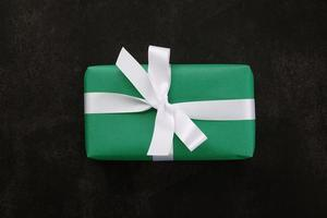 Top view of Christmas gift box wrapped with green paper and white ribbon on grunge background