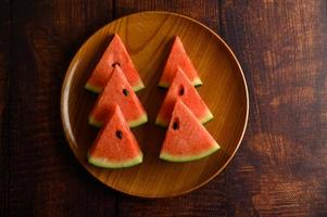 Watermelon cut into pieces on a wooden table