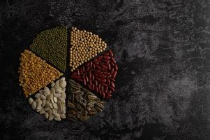 Legumes arranged in a circle on a black cement surface