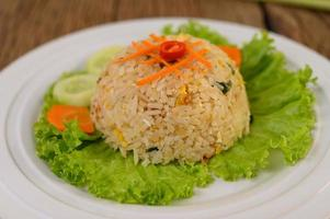 Fried rice on a white plate with lettuce and garnish