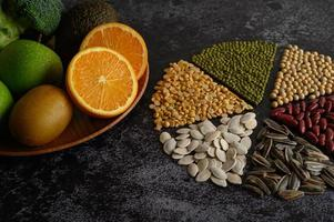 Legumes with oranges, kiwi, and apple on a black background