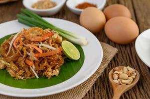 Plate of pad thai shrimp with lime and eggs