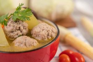 sopa de albóndigas de cerdo rodeada de ingredientes