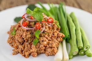 Spicy minced pork salad on green vegetables