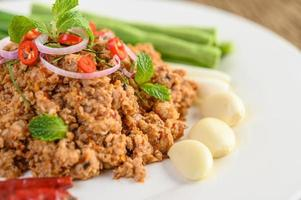 Spicy minced pork salad on green vegetables